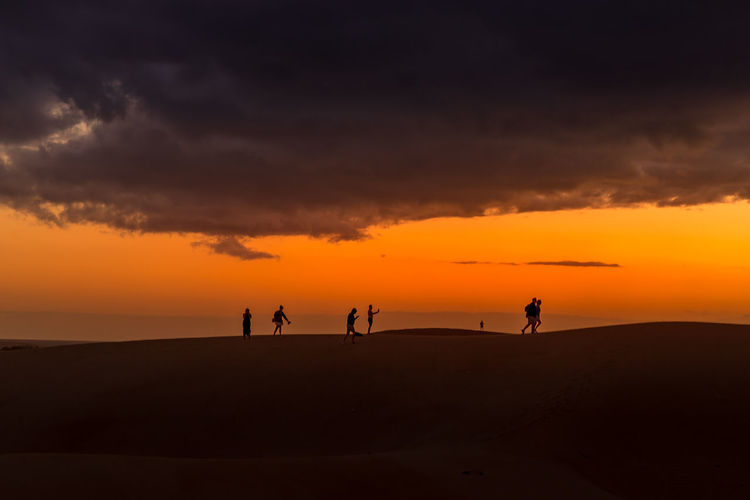 Silhouette people standing on land against sky during sunset