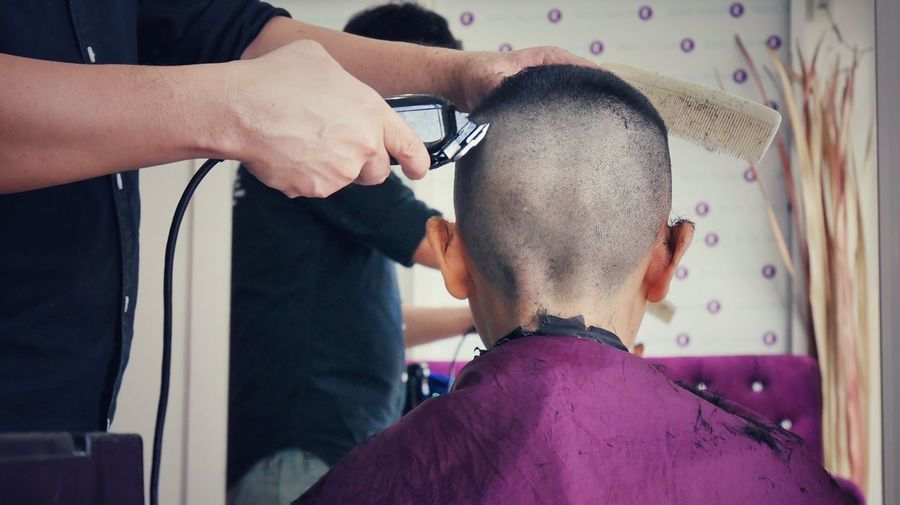 Midsection of barber cutting boy hair in shop