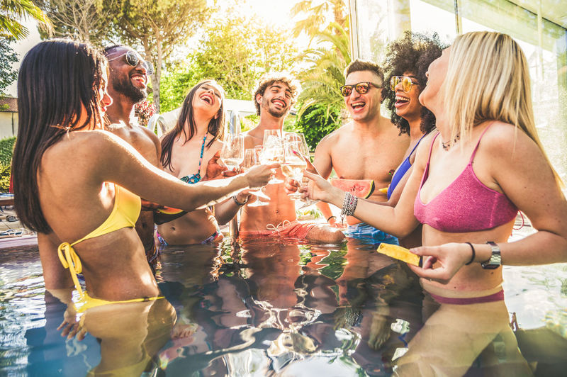 Cheerful friends in swimming pool during social gathering