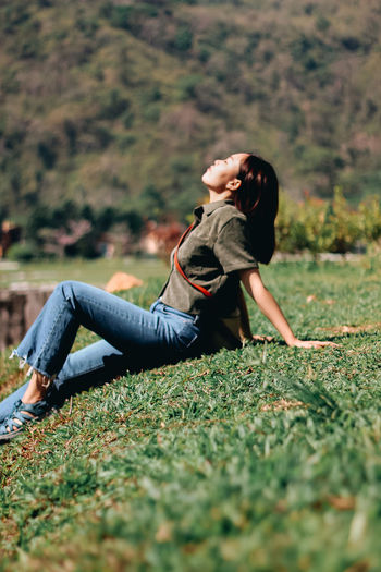 Side view of young woman lying on field