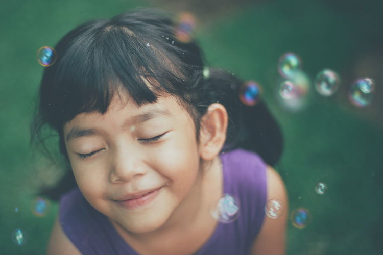 Close-up of smiling girl with bubbles at public park