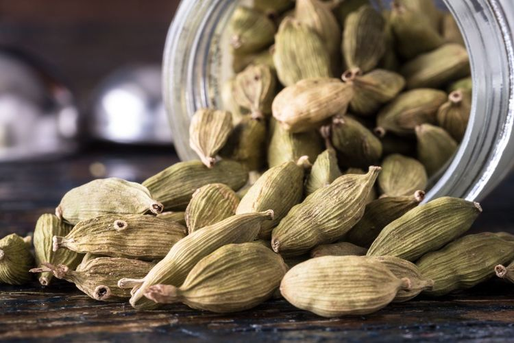 Close-up of cardamom coming out from jar on table
