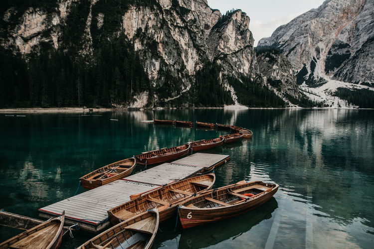 Boat moored on lake against mountain