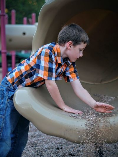 Boy cleaning slide at playground
