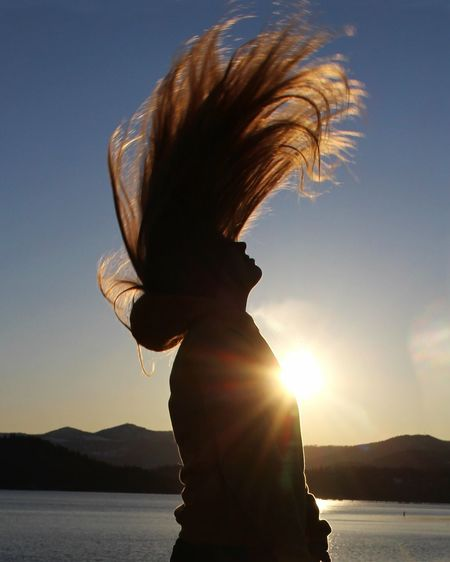 Side view of silhouette woman tossing hair against sky during sunset