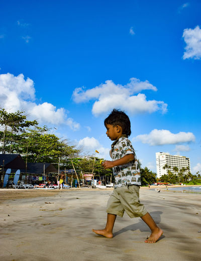 Side view of boy walking at beach against blue sky