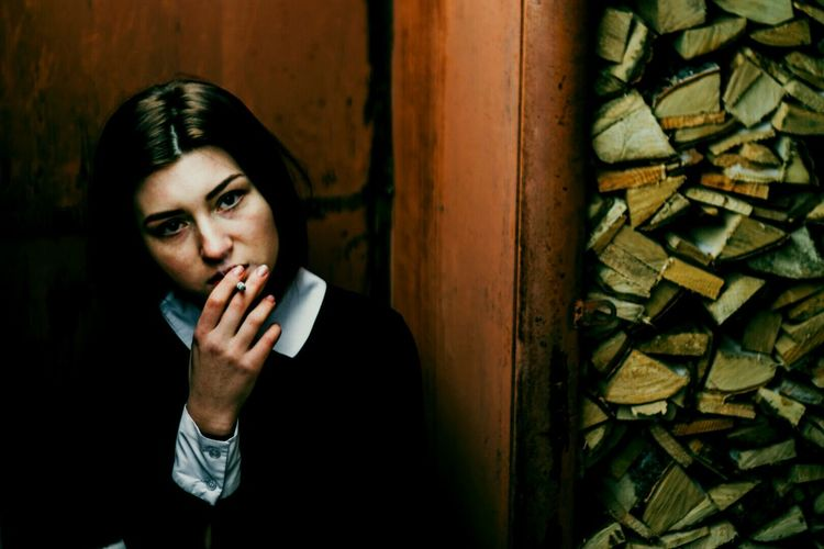 Young woman smoking against rusty wall
