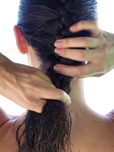 Rear view of woman braiding her hair against white background