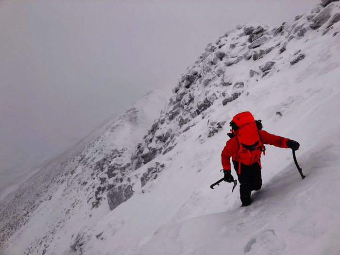 High angle view of man climbing snowcapped mountain