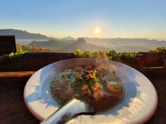 Close-up of food on table against mountains during sunset