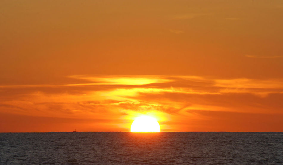 Sunset with the sun on horizon over water at Padang Beach Indonesia Beauty In Nature Cloud - Sky Dramatic Sky Freedom Gold Colored Horizon Horizon Over Water Idyllic Nature No People Orange Color Outdoors Scenics - Nature Sea Seascape Sky Sun Sunlight Sunset Urban Skyline Water