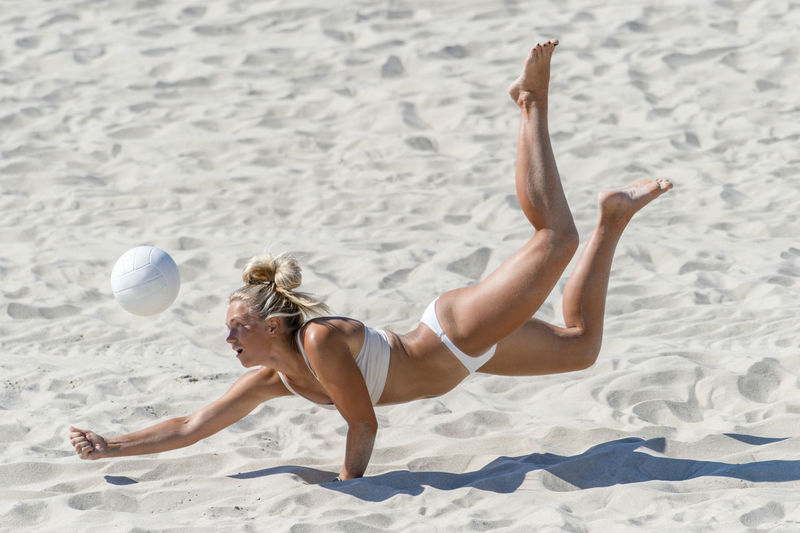 Full length of woman lying down on sand at beach