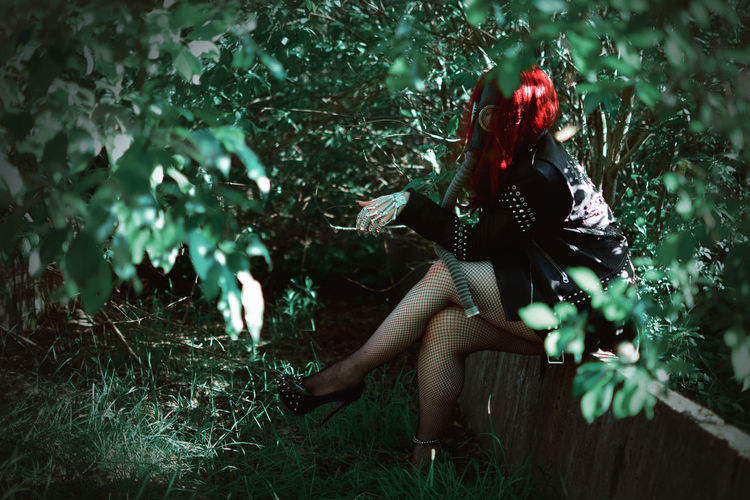 Side view of woman wearing gas mask sitting amidst plants