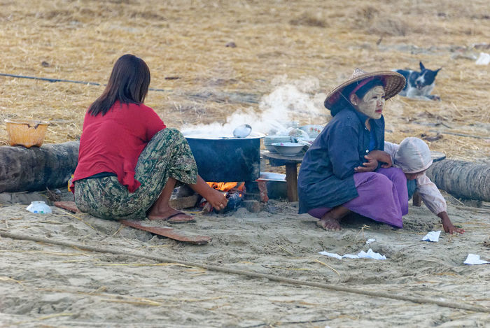 An open air kitchen to warm up inside and outside Rakhine State Adult Beach Child Childhood Day Full Length Girls Lifestyles Men Myanmar Outdoors People Real People Sand Sitting Togetherness Two People Warm Clothing Women
