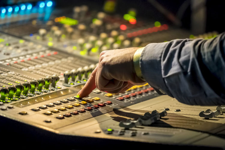 Cropped hand of male dj pressing push button on control panel during music concert