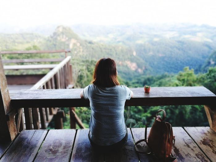 Rear view of woman sitting in balcony against mountains