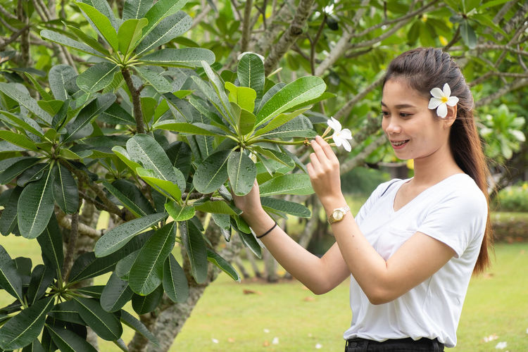 Young woman smiling while standing by tree against plants