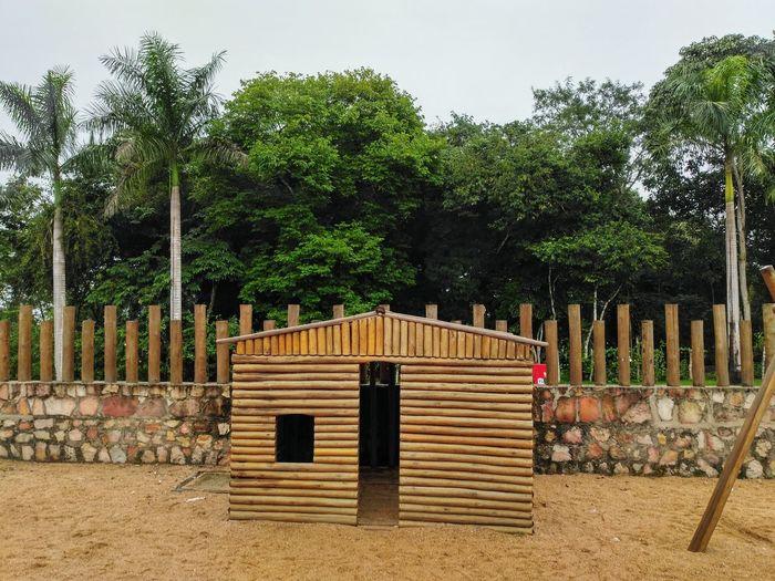 a wooden small house on a playground Playground Wooden House Door Window Fence Gravel Tree Wood - Material Gate Sky Picket Fence
