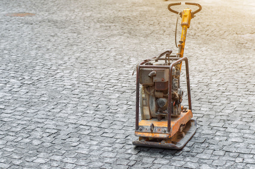 Reversible plate compacts pavement tiles laid on the street Car City Cobblestone Construction Equipment Construction Industry Day Footpath High Angle View Land Vehicle Machinery Mode Of Transportation Nature No People Outdoors Paving Stone Road Sidewalk Single Object Street Transportation Yellow