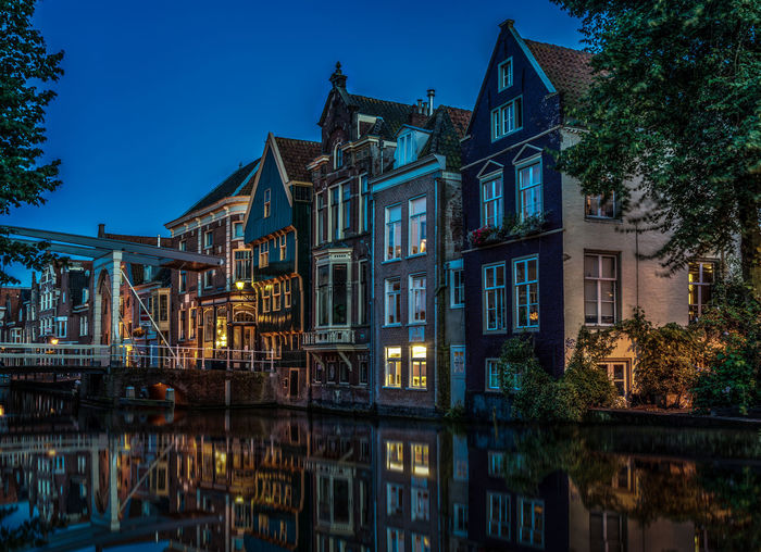Residential Buildings Reflecting In Canal Against Clear Blue Sky At Dusk