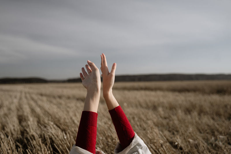 Cropped hand of woman on field against sky