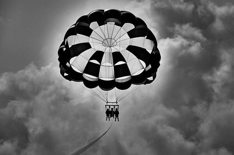 Low angle view of people parasailing against sky