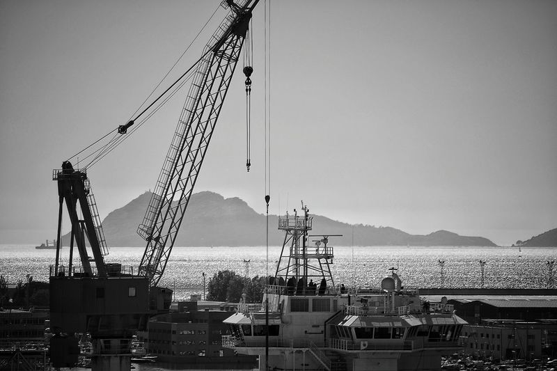 Crane At Construction Site By Sea Against Clear Sky