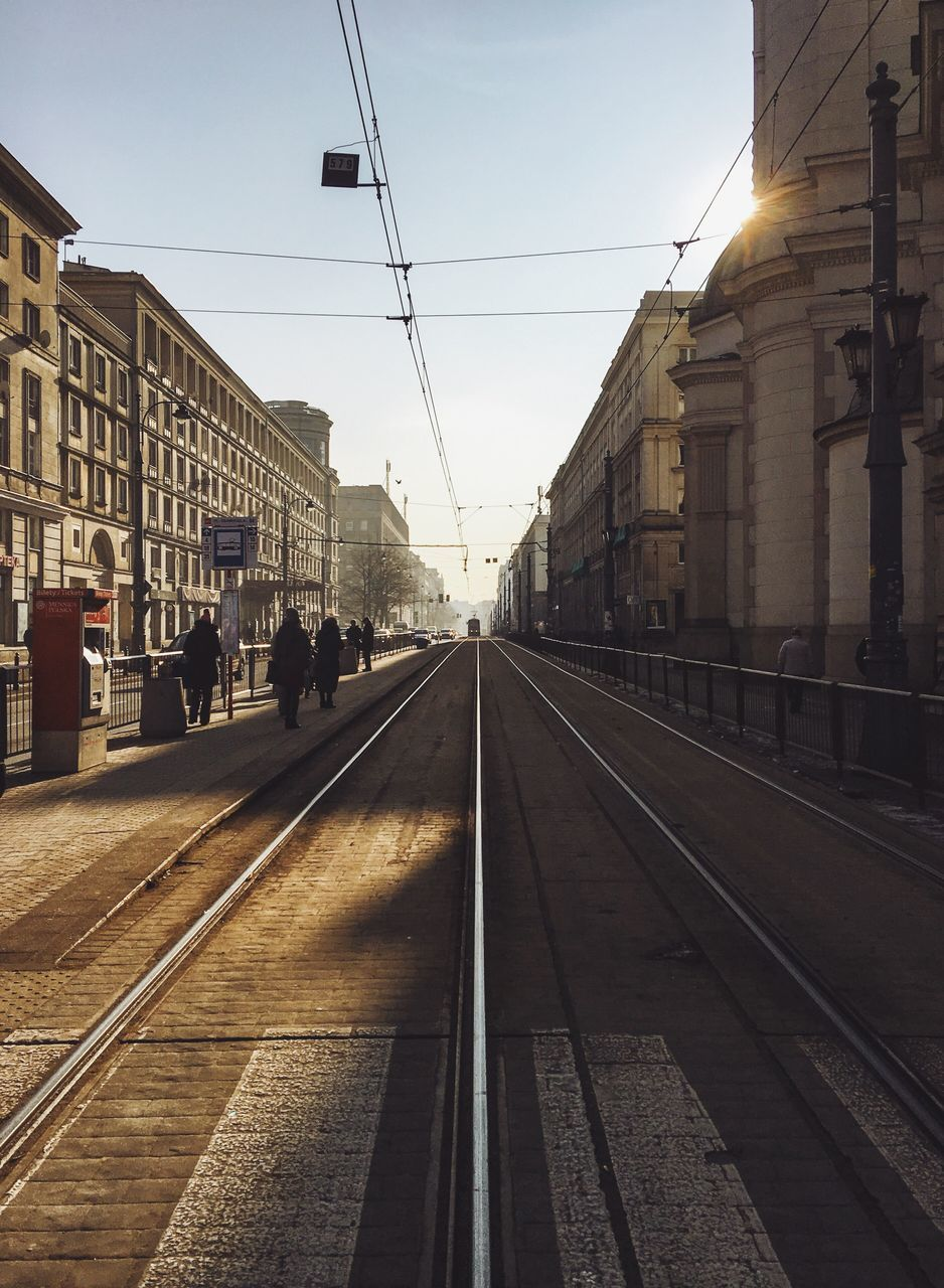 railroad track, transportation, rail transportation, public transportation, cable, real people, built structure, architecture, the way forward, large group of people, railroad station platform, outdoors, building exterior, group of people, sky, day, men, city, clear sky, people