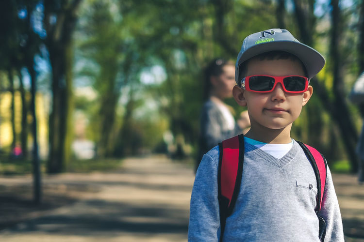 Portrait of boy wearing sunglasses and cap standing in park
