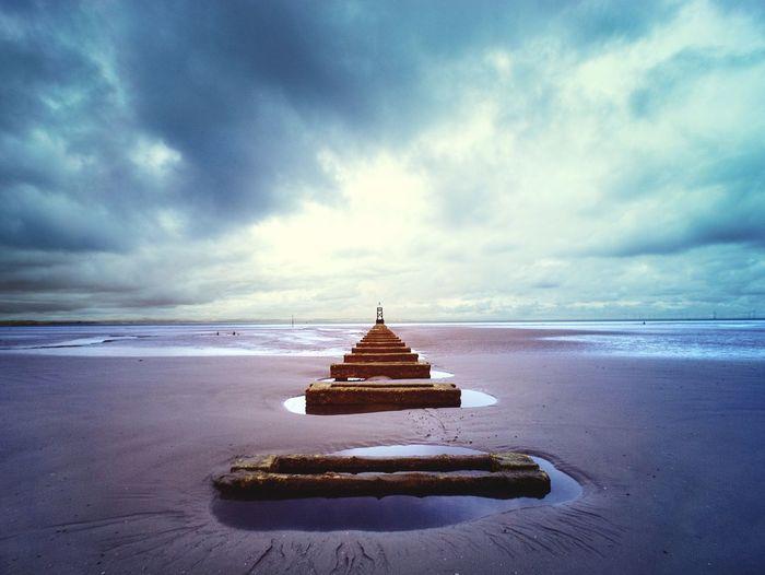 Cross on beach against sky