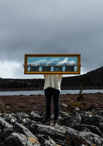 Person holding mirror with reflection while standing on land against cloudy sky