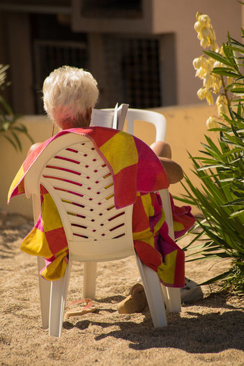 Back View Of Woman Paint The Town Yellow Red And Yellow For Catalan By The Beach! Day Leisure Activity One Person Reading A Good Book Relaxing Moments Tranquil Scene White Chair