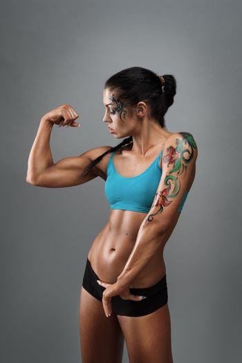 Muscular woman flexing muscles while standing against gray background