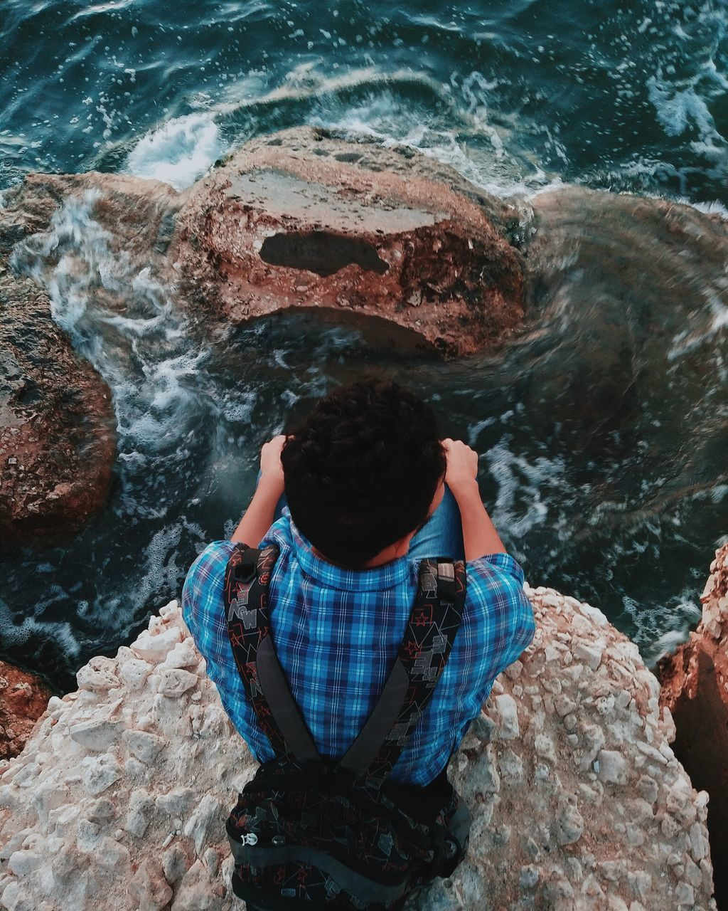 High Angle View Of Young Man Sitting On Cliff Over Sea