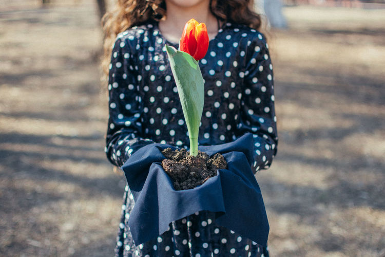 Rear view of woman holding flower standing outdoors