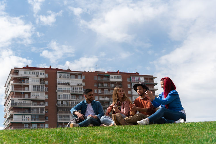 People sitting on grass against the sky