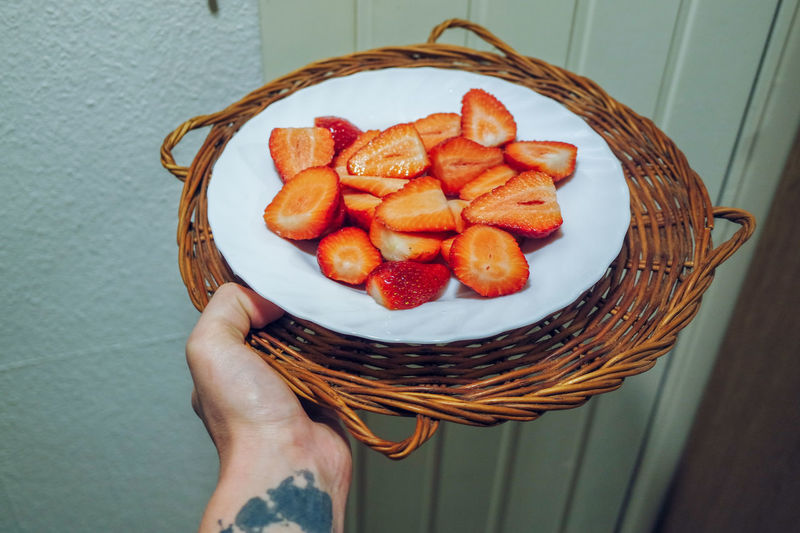Cropped hand of person holding strawberry in plate and basket
