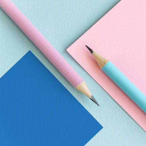 High angle view of pencils with paper on colored background