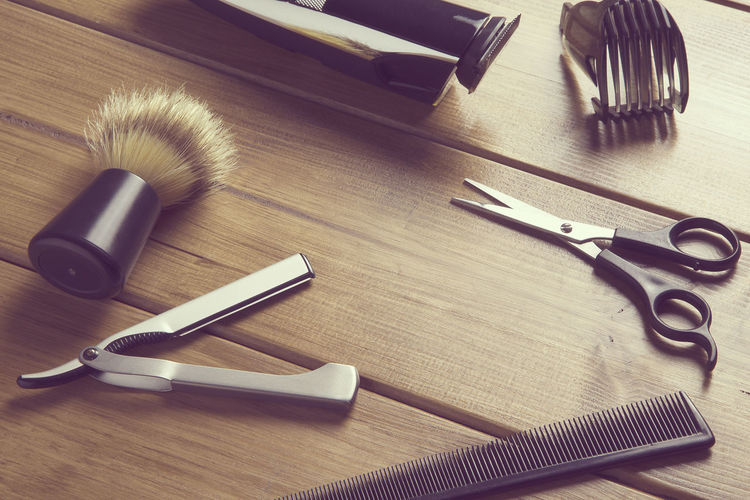High angle view of scissors and comb with razor on table