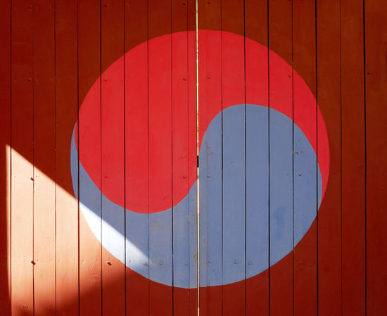 A symbol of Korea's iconic Taegeuk mark drawn on the old door. ASIA Kora National Design Door Drawn Flag Geometric Shape Iconic Old Pattern Red Shadow Shape Symbol Taegeukgi Wood - Material