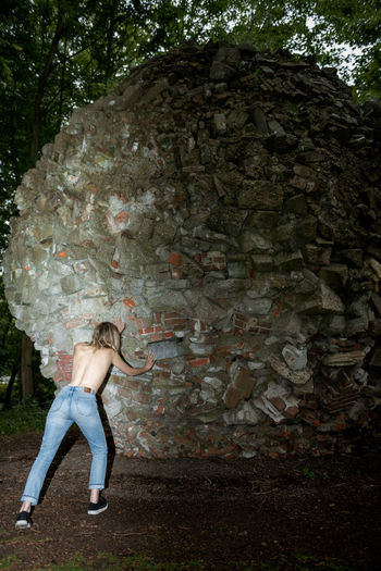 Rear view of shirtless woman pushing rocky structure at park