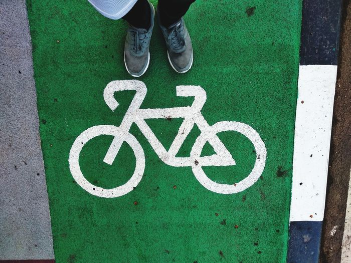 Low section of person standing by bicycle sign on road