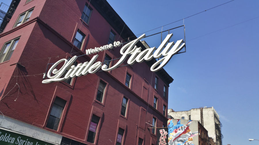 a sign announcing the entrance to Little Italy along Canal Street in New York Architecture Building Exterior City Life Composition Exterior Information Low Angle View Perspective Street Urban