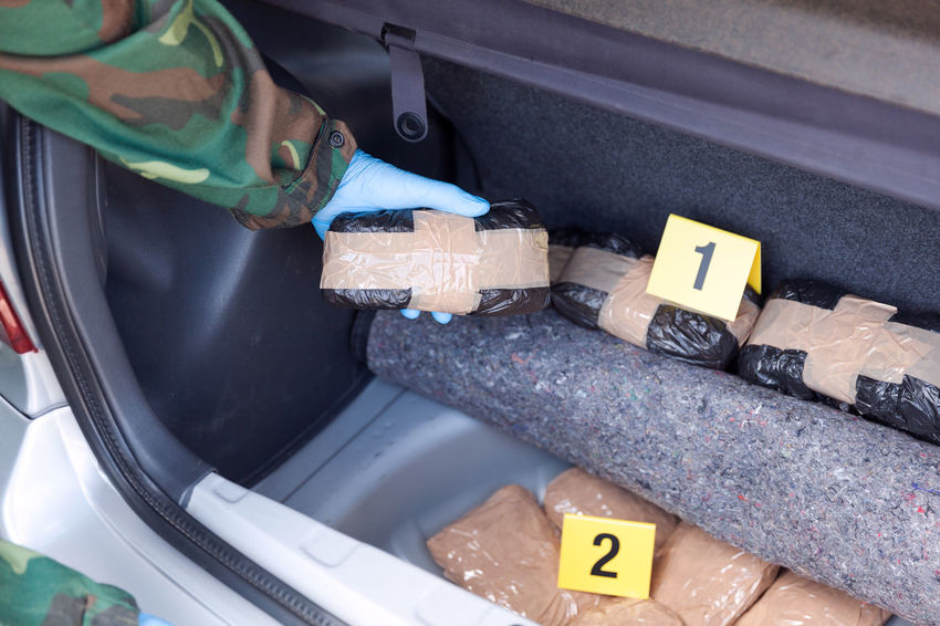 Police officer holding drug package found in the trunk of a car. Crime scene evidence markers Cannabis Crime Crime Scene Drug Drug Enforcement Drug Trafficking Uniform Arrest Car Cartel Cocaine Compartment Evidence Marker Gloved Hand Heroin Illegal Law Enforcement Marijuana Narcotics Number Package Police Smuggling Stash Trunk
