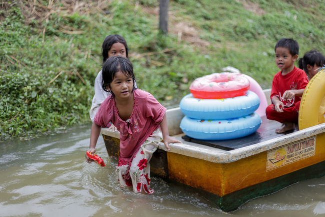 flood victims at kelantan Flood Victim Adult Boys Child Childhood Day Elementary Age Front View Full Length Fun Girls Leisure Activity Lifestyles Looking At Camera Mid Adult Women Outdoors People Portrait Real People Sitting Smiling Togetherness Water