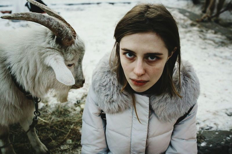 Portrait of young woman with goat in winter