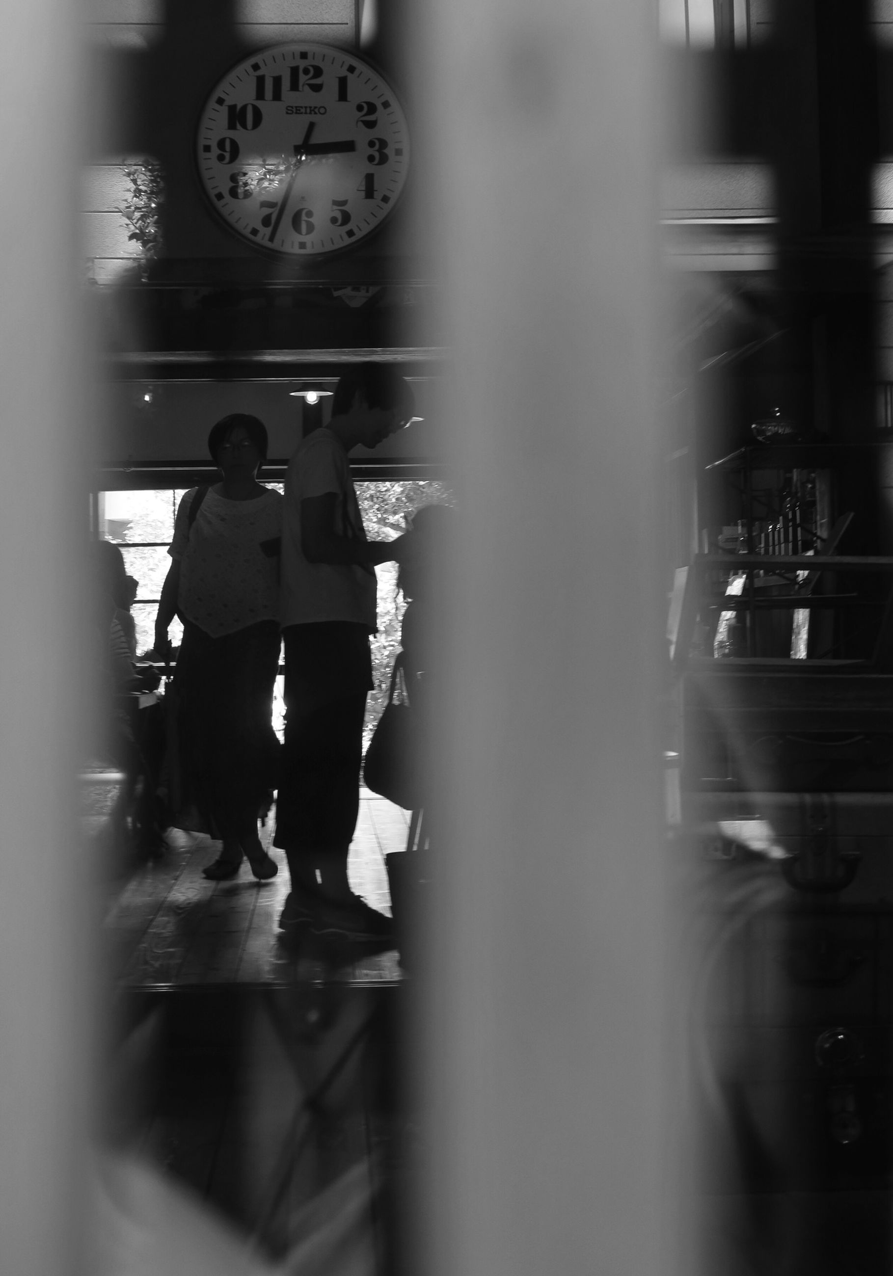 clock, time, real people, indoors, focus on background, selective focus, occupation, two people, men, standing, women, working, day, young adult, clock face, people
