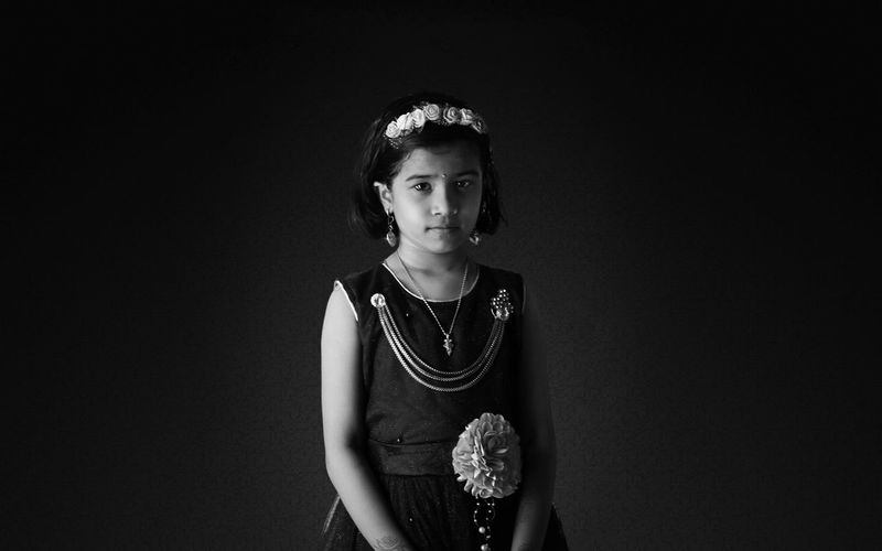 Portrait Of Girl Wearing Dress And Headband Standing Against Black Background