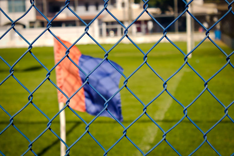 Flag waving on soccer field seen through chainlink fence