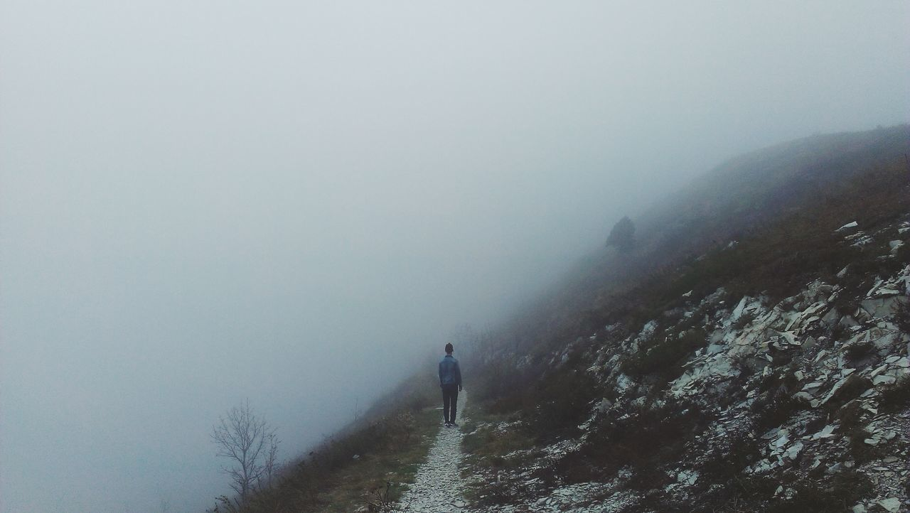 Rear view of man standing on fog covered mountain